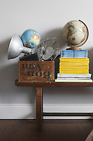 Childhood globes and a collection of old National Geographics are piled on a wooden stool