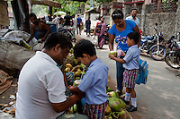 Razia Shabnam (in blue) buys coconut juice as she picks her son, Saihaan, up from the St. Thomas School in Kidderpur after finishing her boxing training sessions in Calcutta, West Bengal, India. Razia Shabnam, 28, was one of the first women boxers in Kolkata. She was also the first woman in her community to go to college. She is now a coach and one of only three international female boxing referees in India.  Photo by Suzanne Lee for Panos London