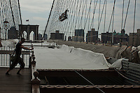 A tourist stretches at the Brooklyn Bridge while it remains under maintenance one day before its 130th anniversary in New York,  May 23, 2013, Photo by Eduardo Munoz Alvarez / VIEWpress.