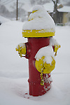 March 5, 2015. Merrick, New York, United States. A red and yellow fire hydrant has been partly cleared of snow during yet another snowfall  on the south shore of Long Island, which is receiving the heaviest snow on L.I., with an accumulation of 6 to 8 inches expected. Many school closed due to hazardous travel conditions, and a Winter Weather Watch is in effect until 7 PM.