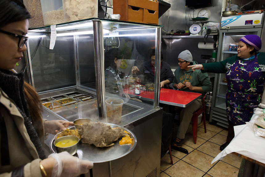 Kamala Gauchan, who opened Dhaulagiri Kitchen, a tiny Nepalese restaurant in Jackson Heights, about two years ago, tends to customers. <br /> <br /> Danny Ghitis for The New York Times