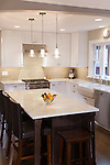 Shaker-style white cabinetry and white Carrera marble create a crisp, clean look in this newly remodeled kitchen.