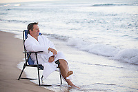 Good looking middle aged man in a white robe sitting in a folding chair on the beach in Fort Lauderdale, Florida