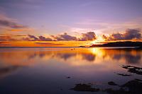 A new day dawns in purple and gold over calm seas at Anini Beach, Kaua'i.