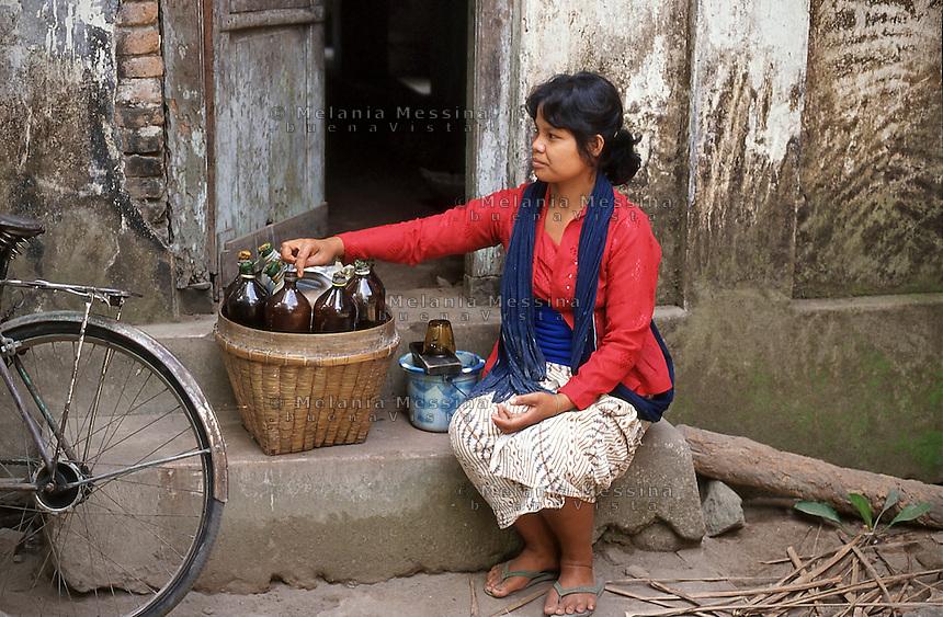 Indonesia, Java island, jamu seller offers her medicine in the village for primary health care.<br /> Indonesia; Giava, venditrice di jamu (medicina a base di erbe) durante il suo giro nel villaggio.