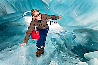 A woman enjoys a beautiful ice cave on Franz Josef Glacier - Westland National Park, West Coast, New Zealand