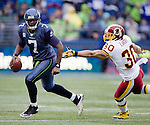 Seattle Seahawks quarterback Tarvaris Jackson scrambles away from Washington Redskins safety LaRon Laundry r at  CenturyLink Field in Seattle, Washington on November 27, 2011.  ©2011 Jim Bryant Photo. All Rights Reserved.