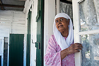 A lady at the front door to her fine Creole home in Mahebourg.
