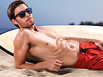 Young man with a surfboard lying on the sand at the beach, wearing sunglasses