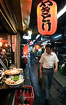 "Customers enjoy a variety of cuisine at an establishment in Omoideyokocho, or ""Remeniscenses Alley"" -- sometimes referred to as Shonbenyokocho (Piss Alley) in Shinjuku, Tokyo, Japan. Omoideyokocho began life immediately after World War II as part of the black market area around Shinjuku station, which also includes the area a little further from the station known as Golden Gai. Due to its low rents and relative seclusion, the area was a magnet for all sorts of illegal activity and was an extension of what is known in Japan as the ""mizu shobai"", which is often rendered in English as the ""floating world"" but literally means the the ""water business"". During the period immediately following Japan's occupation by the Allied Forces, illegal activities, such as prostitution, in the area was outlawed, and the tiny establishments were taken over by proprietors, mostly women known as ""mama-san"",  who dedicated their business energy into selling drink and cheap but good food.  The alley, which houses some 40 eateries, is popular with salaried workers and young students and musicians and artists."