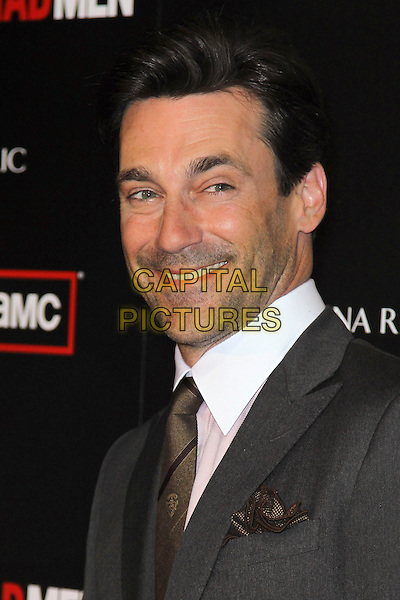 "JON HAMM.at the Season 4 premiere of AMC's ""Mad Men"", Mann Chinese 6 Theatre. Hollywood, CA, USA, July 20th, 2010. .portrait headshot stubble facial hair tie pink white collar shirt grey gray smiling brown .CAP/CEL.©CelPh/Capital Pictures."