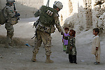 Children line up to shake hands with Cpl. Mitch Niles during a patrol in Zhari district in Kandahar province, Afghanistan. Niles is a soldier with November Company, 3rd Battalion, Royal Canadian Regiment. Despite daily skirmishes with Taliban fighters in the area, the soldiers often encounter many friendly villagers as well. Sept. 28, 2008. DREW BROWN/STARS AND STRIPES