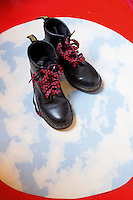 A pair of Dr Martens with personalised laces on a circle of lino