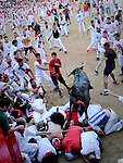 A fighting cow leaps over bull runners in the Plaza de Toros following the sixth Running after the sixth San Fermin Festival bull run, on July 13, 2012, in Pamplona, northern Spain. The festival is a symbol of Spanish culture that attracts thousands of tourists to watch the bull runs despite heavy condemnation from animal rights groups. (C) Pedro ARMESTRE. (c) Pedro ARMESTRE