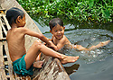 Children enjoy a swim amid the canal to reach a boat.