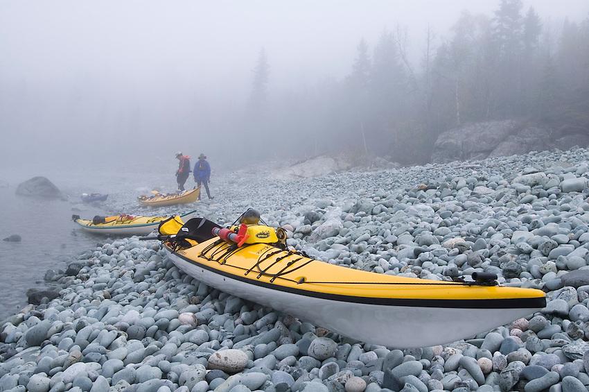 Sea kayaker on a cobblestone beach in the fog in Lake Superior Provincial Park near Wawa Ontario Canada.