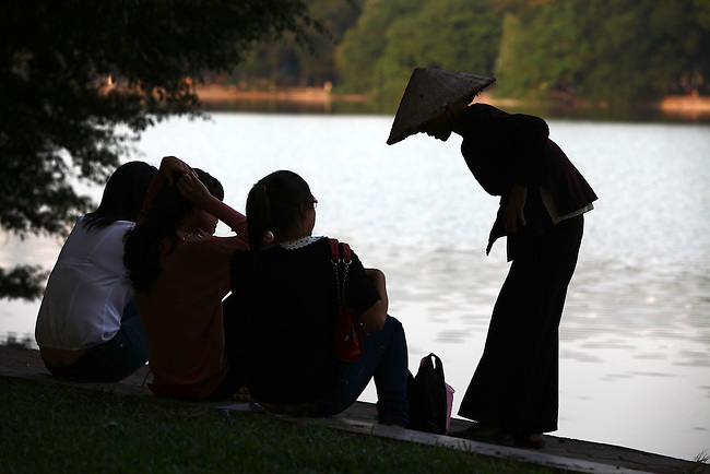 An elderly woman in traditional dress talks to young women sitting along the shore of the Lake of the Restored Sword in Hanoi, Vietnam. Nov. 12, 2012.