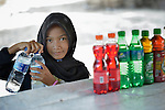 Ten-year old Fathan Nur Selani helps arrange bottles in her mother's small business on the beach at Lhok Me, in Indonesia's Aceh province. The girl's mother, Rusmiati, sells coconuts and soft drinks to tourists on the beach. The 2004 tsunami struck the coastal village when Fathan was just three weeks old. YEU, a member of the ACT Alliance, worked with the village to build new houses in a safer area, as well as help revitalize their income generating activities, including Fathan's mother's small business. The tsunami killed 221,000 people in Aceh province and left more than 500,000 displaced.<br /> <br /> Parental consent obtained.