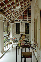 Striped black-and-white blinds shield the dining area of the verandah from the mid-day sun and it is also cooled in true colonial style by an old-fashioned ceiling fan