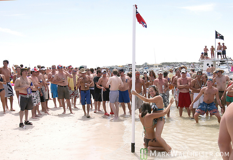 Memorial Day weekend celebrants watch two girls pole dancing on a Confederate flag adorned pole that was erected in the surf at Dog Islance for the weekend long White Trash Bash at Dog Island off the coast of Carrabelle Sunday May 27, 2007.    (Mark Wallheiser/TallahasseeStock.com)
