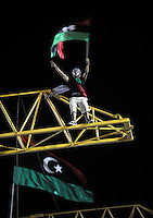 A man stands on a crane waving a flag at Martyrs' Square in Tripoli. After a six month revolution, rebel forces finally managed to break into Tripoli and have taken control of Bab al-Aziziyah, Col Gaddafi's compound and residence. Few remain that are loyal to Gaddafi in the city; it is seeming that the 42 year regime has come to an end. Gaddafi is currently on the run.