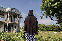 """Indonesia – Sumatra – Banda Aceh – Lampaseh – 49-year-old Yusnida looks at the remains of  a villa destroyed by the tsunami where she was stranded for a few minutes between the second and the third wave before the stream brought her to the open sea. An oyster collector and the mother of three children, two of whom were killed by the waves, Yusnida spent almost twelve hours at sea during the tsunami, floating thanks to a pair of plastic containers under her armpits. She was collected in the evening by some fishermen, who gave her clothes and brought her to a nearby hospital, where she spent the following six months recovering from several injuries. Yusnida was able to return to her new house two years after the tsunami, only to find the atmosphere of the village dramatically changed. The thousands of people who died had been replaced by several newcomers, who Yusnida felt could never understand the tragedy of what had happened. """"In the first year after the tsunami I used to ask myself 'Why did I survive? Wasn't it better to go together with my sons?'"""