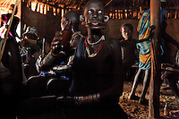 A Mursi woman licks the last drop of beer off of her lip plate in a bar in Kibbish, the last village at the end of the last road in the upper Omo Valley.  Outside police are walking up and down the main dirt road of the town with megaphones telling men to check their AK-47's at the police station.  Obviously the man in the background of this photo is ignoring their message.