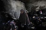 A Palestinian woman cries as she inspects a burnt room after a fire swept over a house in Gaza City on January 31, 2013. Hazem Dheir, his wife Sahar and their four young children were killed in the fire that is believed to have started by an electrical fault. Photo by Ashraf Amra