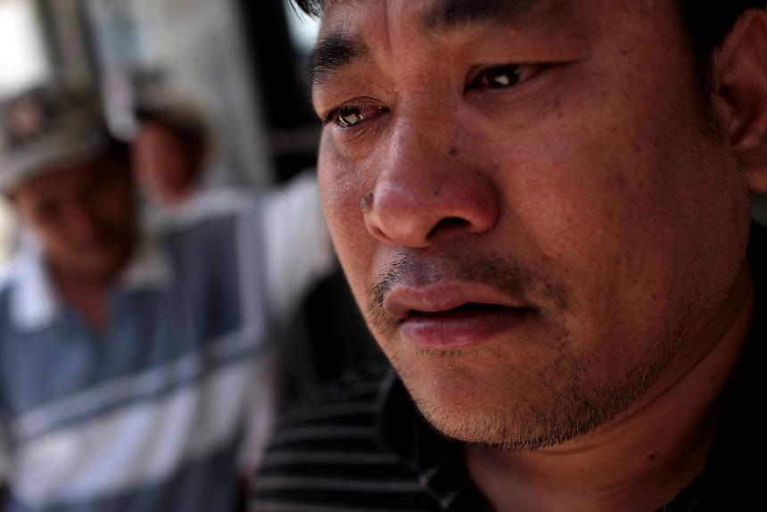 Shrimpboat captain Minh Vo cries after waiting for over four hours for financial support from Catholic Charities in New Orleans East, LA on May 21, 2010. He received a $100 grocery check for his family of six. His wife was forced to find a job after his commercial shrimp boat was grounded because of the oil spill. The Vietnamese fishing community have struggled to survive after the shrimping industry shut down three weeks earlier after the BP oil spill in the Gulf of Mexico.