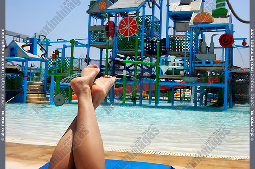 Bare feet of young woman relaxing on sunbed near pool in water park