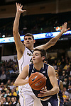 24 February 2016: Notre Dame's Steve Vasturia (below) passes the ball under Wake Forest's Konstantinos Mitoglou (GRE) (behind). The Wake Forest University Demon Deacons hosted the University of Notre Dame Fighting Irish at Lawrence Joel Veterans Memorial Coliseum in Winston-Salem, North Carolina in a 2015-16 NCAA Division I Men's Basketball game. Notre Dame won the game 69-58.