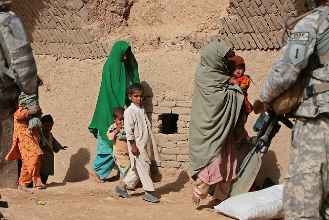 Women and children move into another room of their family compound, as U.S. soldiers carry out a search for Taliban weapons and supplies in the village of Mowshaq in Maiwand district, Kandahar province, Afghanistan. April 1, 2009. DREW BROWN/STARS AND STRIPES