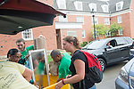 President and First Lady McDavis and Go Green volunter Michael LIvely (Back Left) help sophomore Laura Conley (Right) move into her residence hall. Photo by Ben Siegel