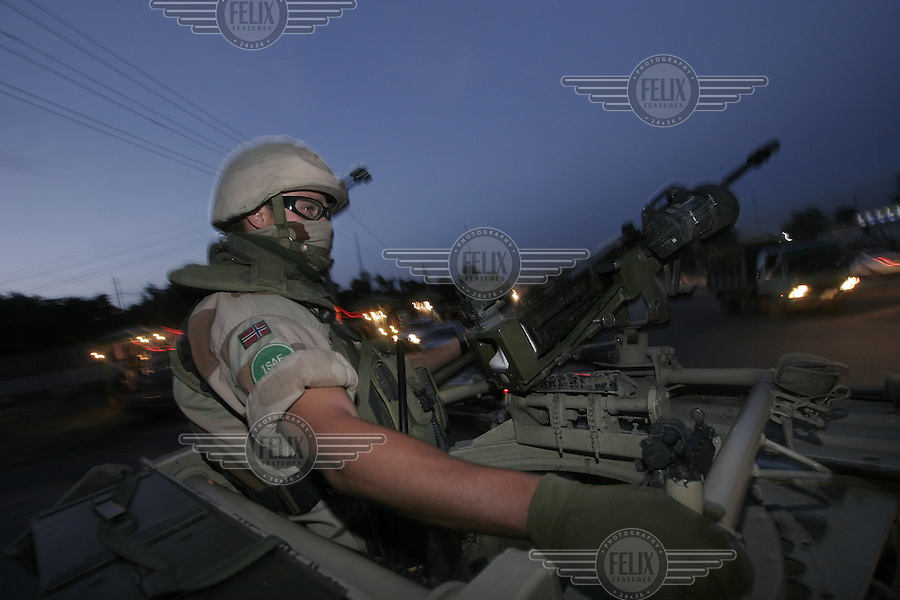 A soldier manning a machine gun atop a vehicle belonging to the Norwegian ISAF troops, in the center of Kabul.  ISAF, the International Security Assistance Force, is a peacekeeping mission affiliated to the United Nations (UN) and NATO.