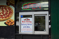 A hiring sign for a delivery driver with bike in a window of a Papa John's Pizza franchise in Washington Heights in New York on Sunday, August 12, 2012. (© Frances M. Roberts)