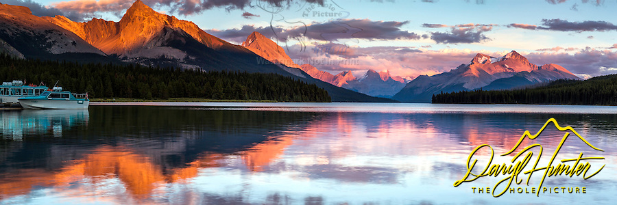 Maligne Lake Sunset Panorama, the Queen Elizabeth Range reflecting in the calm waters of the lake. <br /> <br /> This is a large file and can be printed as large as 9 feet by 3 feet at 150 DPI.  If you don't like the boats a cropped version can be arranged.