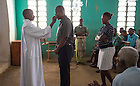 Augustin Dantil (left), the chapel sacristan whose daughters Clara and Asmide attend College Saint Gabriel, gives communion to Pierre-Louis Joizil, the school's 36-year-old founder and headmaster.