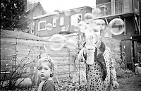 Fun in the back yard. Photograhers daughter is blowing bubbles at the camera.