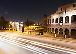 At night, passing traffic illuminates the ancient Roman Colosseum and nearby Constantine's Arch, with the hills of the Forum beyond.
