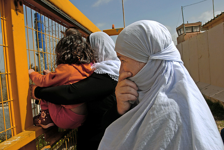 Relatives of Arwad Abu Shaheen stand at the border fence watching Arwad crossing to Syria, at the Quneitra border-crossing, Israel-Syria border.