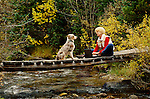 Australian Shepherd dog looks on as woman uses laptop computer on bridge over creek, San Isabel National Forest, Colorado, <br /> MODEL RELEASED, PROPERTY RELEASED
