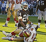 Oakland Raiders defensive back Charles Woodson (24) and San Francisco 49ers wide receiver Terrell Owens (81) on Sunday, November 3, 2002, in Oakland, California. The 49ers defeated the Raiders 23-20 in an overtime game.