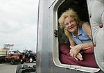 Mickey McGregor, from Mesquite, Tx., peers out from her truck at the Truckers Jamboree held in Walcott, Iowa, every year.  This event was in 2006.   McGregor has been on the road with her husband since 1974.  Her husband has been driving since 1957.  &quot;After the last child got married (McGregor had 13 children), Dad told the kids that mom was going to be a wife again and learn to drive a truck,&quot;  McGregor said.  McGregor called the truck they drive a &quot;junkyard dog&quot; because it is a combination of three different trucks.