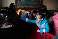 January 31 2014, Chinese New Year celebrations. A young girl is touching the head of a propiciatory statue of a rat in the Lama Temple of Beijing in order to gain luck in the coming year.