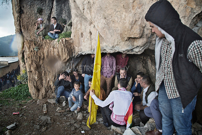 21/03/15 -- Akre, Iraq -- Young people from Akre take shelter from the rain under a rock as they wait to start Newroz celebrations