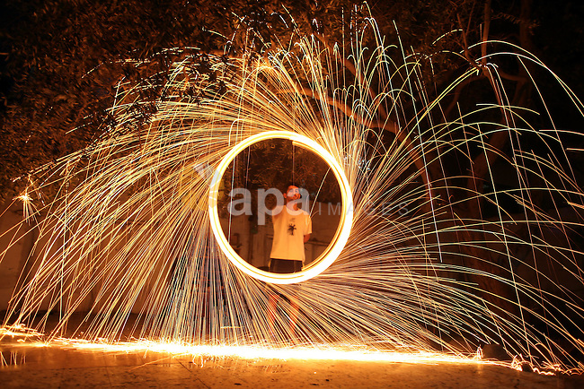 A Palestinian youth plays with fire crackers as he celebrates the third day of the Muslim fasting month of Ramadan, in Gaza City on July 1, 2014. Muslims around the world celebrate Ramadan, the holiest month in the Islamic calendar, in which they abstain from eating, drinking and conducting sexual relations from sunrise to sunset. Photo by Ali Jadallah