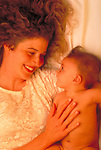 smiling mother lying in bed with nude infant