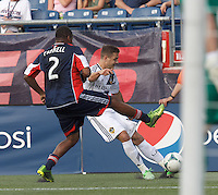 LA Galaxy substitute midfielder Robbie Rogers (14) crosses the ball as New England Revolution defender Andrew Farrell (2) defends. In a Major League Soccer (MLS) match, the New England Revolution (blue) defeated LA Galaxy (white), 5-0, at Gillette Stadium on June 2, 2013.