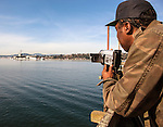 Frank Jenkins films the USS Ranger as it is towed from Puget Sound Naval Shipyard's Inactive Ship Maintenance Facility in Bremerton, WA. on March 5, 2015. Jenkins served as a jet engine mechanic from 1976 to 1980 onboard the carrier, which is en route to be scraped at International Shipbreaking in Texas. The aircraft carrier was active from 1957 to 1993, when it entered the mothball fleet. The Navy announced a deal Dec. 22 to pay a penny and the value of the ship's scrap metal to take it away. It must make a five-month, 16,000-mile trip around South America because it can't fit through the Panama Canal.  ©2015. Jim Bryant Photo. All RIGHTS RESERVED.