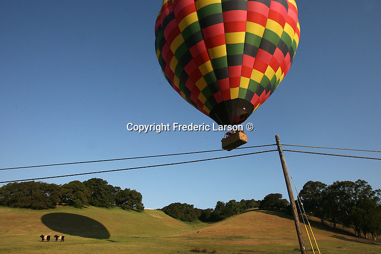 A hot air balloon sails dangerously close to a wire in Napa Valley, California.